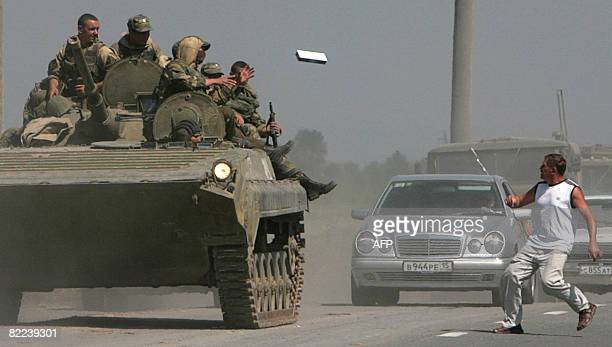 A man throws a pack of cigarettes to Russian soldiers sitting on top of an armored vehicle on their way to South Ossetia on August 10 not far from...