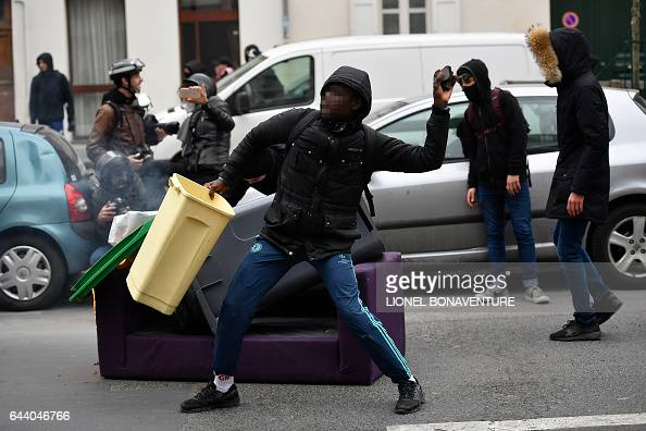 A man throws a projectile at riot police during a protest of students against police brutality following the alleged rape of Theo in Paris on...