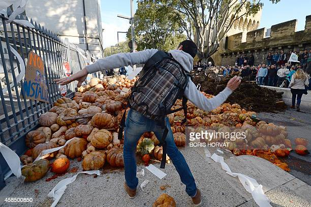 A man throws a projectile next to pumkins dumped in front of the Vaucluse prefecture in Avignon southeastern France on November 5 during a...