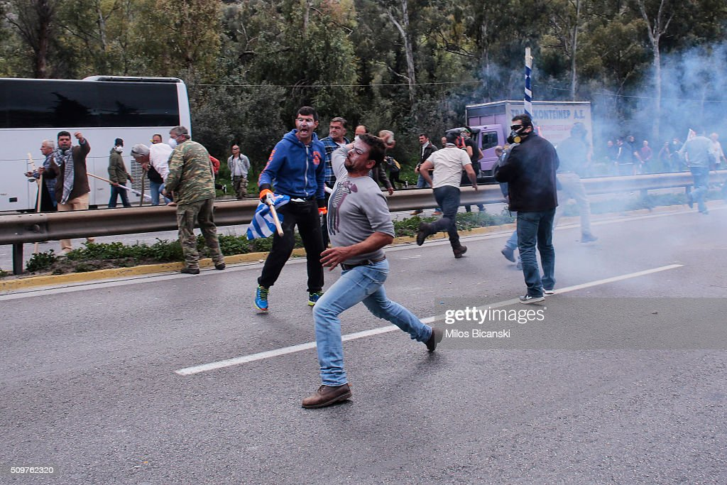A man throws a rock as clashes break out on the highway after police blocked the road from a planned pension reform protest outside the Agriculture ministry on February 12, 2016 in Athens, Greece. Around reportedly 800 protesters from Crete gathered outnumbering police who were armed with teargas.