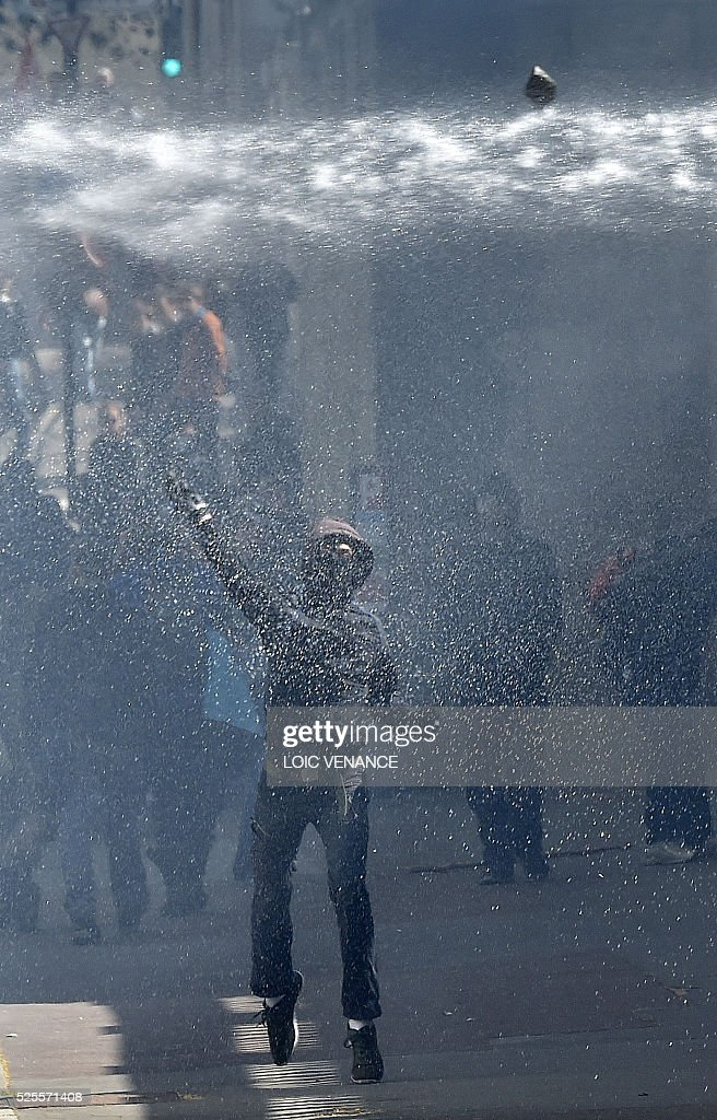 A man throws a stone as he is watered by a water canon during a demonstration against the French government's proposed labour reforms on April 28, 2016 in Nantes. Protests turned violent in Paris and other French cities today as tens of thousands of workers and students made a new push for the withdrawal of a hotly contested labour bill. / AFP / LOIC