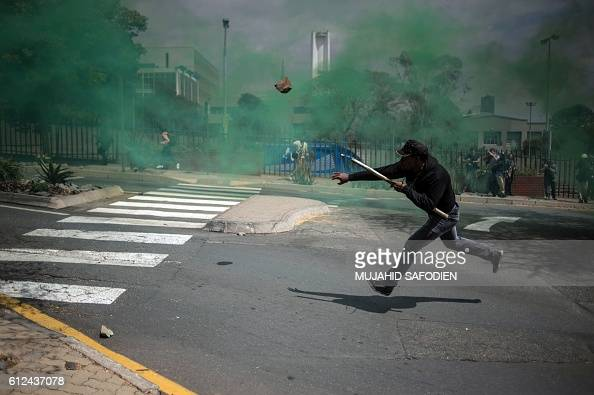 TOPSHOT A man throws a stone during a mass protest of the Fees Must Fall movement at the University of Witwatersrand in Johannesburg on October 4...