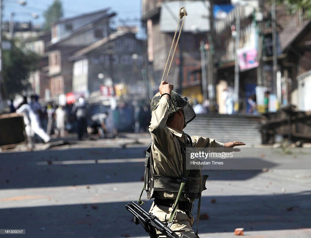 CRPF man throws a stone with a sling during clashes with Kashmiri protestors clash on September 20, 2013 in Srinagar, India. Police fired dozens of tear smoke shells and pellets to disperse hundreds of youth who clashed with them after Friday afternoon congregational prayers in Srinagar. The youth were protesting the civilian killings and continuous curfew in Shopian town, 50 Km south of Srinagar