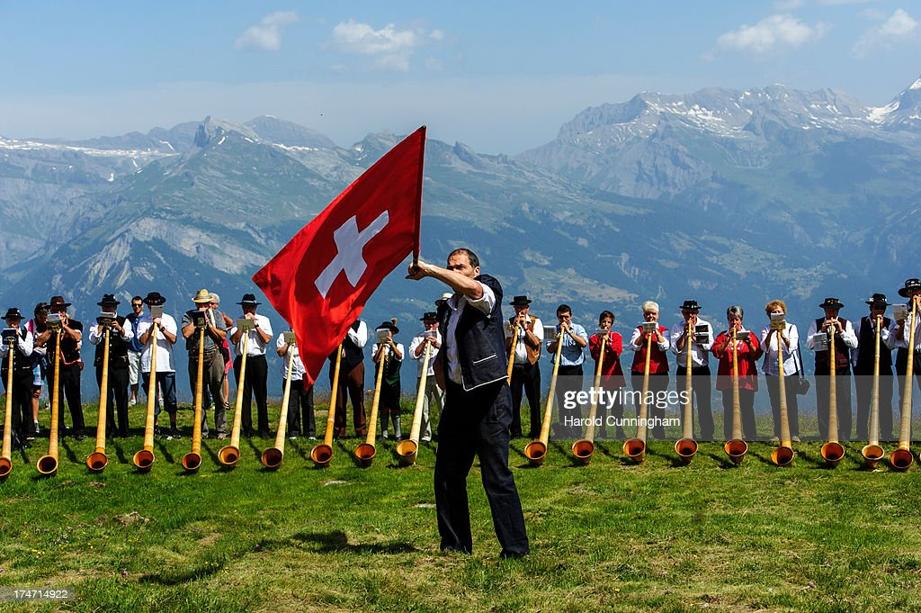 A man throws a Swiss flag as alphorn players perform on July 28, 2013 in Nendaz, Switzerland. About 150 alphorn blowers performed together on the last day of the international Alphorn Festival of Nendaz. The Swiss folkloric wooden wind instrument was used in most mountainous regions of Europe by mountain dwellers as signal instruments.