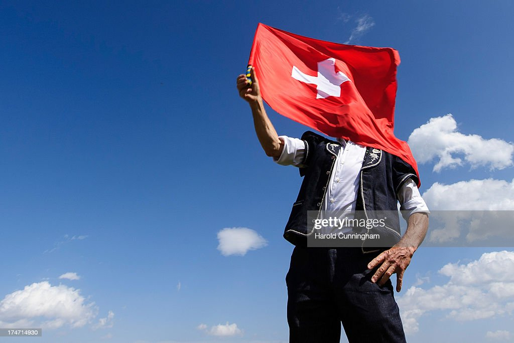 A man throws a Swiss flag on July 28, 2013 in Nendaz, Switzerland. About 150 Alphorn blowers performed together on the last day of the international alphorn Festival of Nendaz. The Swiss folkloric wooden wind instrument was used in most mountainous regions of Europe by mountain dwellers as signal instruments.