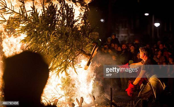 A man throws a tree on a burning pile of trees at the Museumplein in Amsterdam on January 5 during an annual ceremony of Christmas trees' burning AFP...
