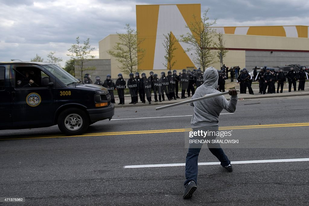 A man throws a wood board at police on April 27 2015 in Baltimore Maryland Violent street clashes erupted in Baltimore after friends and family...