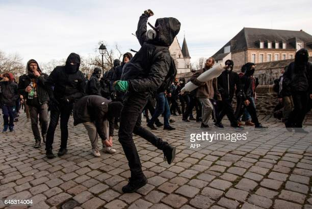 A man throws an object at police during a demonstration against the visit of French presidential election candidate for the farright Front National...