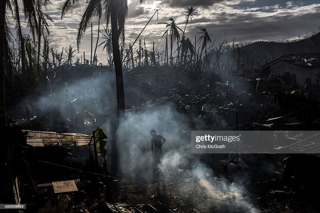 A man throws debris onto a fire as he cleans up his home in Tanauan on November 19 2013 in Leyte Philippines Typhoon Haiyan which ripped through the...
