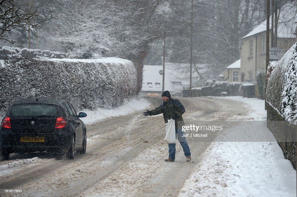 A man throws down salt following recent snowfall on February 13, 2013 in Blanefield, Scotland. Weather forecaster have issued a yellow weather warning of up to 10cm of snow on higher routes, with the possibility of travel disruption.