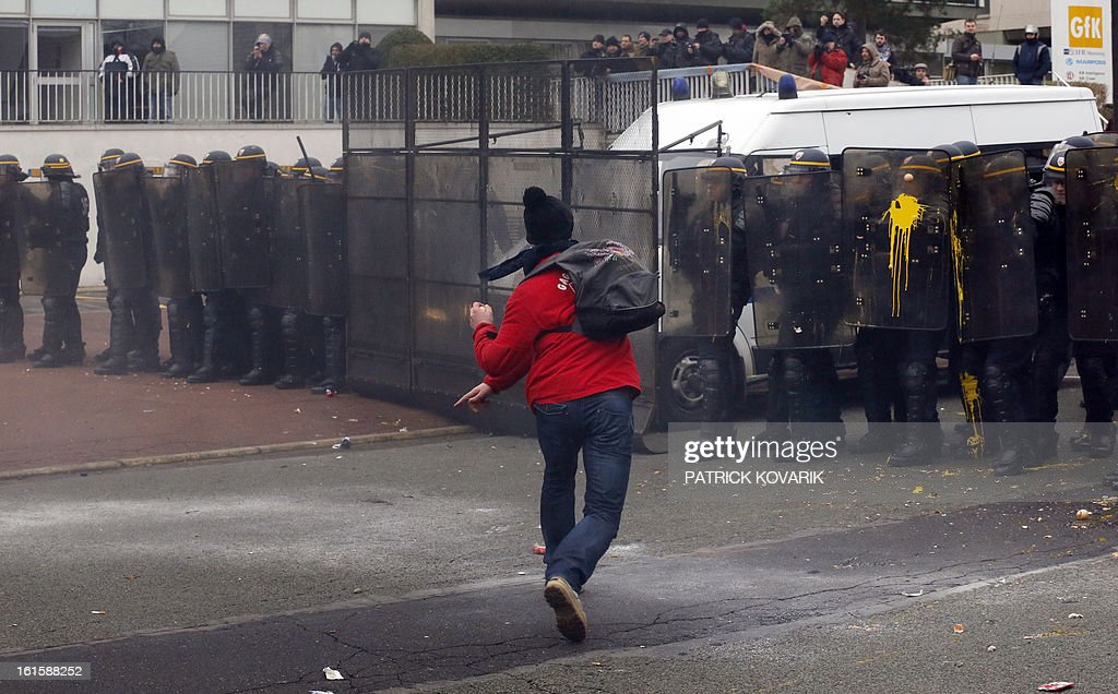 A man throws eggs on the shields of anti-riot police as US Goodyear Tire & Rubber workers demonstrate in front of the group's headquarters in France, in Rueil-Malmaison, a Paris suburb, on February 12, 2013, at the time of an extraordinary central works council on the plan to shut down Goodyear's plant in Amiens, northern France. 'Closing the factory is the only option after five years of unsuccessful negotiations,' said a French-language statement issued on January 31, 2013 by Goodyear Dunlop Tires France, which employs about 3,200 people in the country across four sites. AFP PHOTO PATRICK KOVARIK