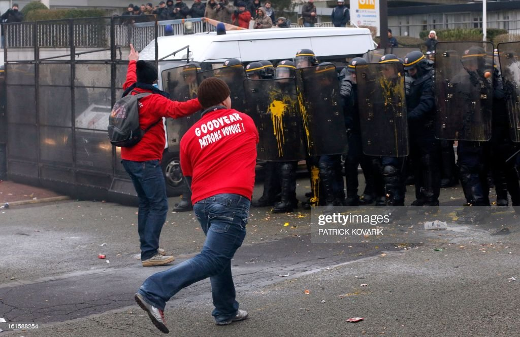 A man throws eggs on the shields of anti-riot police as US Goodyear Tire & Rubber workers demonstrate in front of the group's headquarters in France, in Rueil-Malmaison, a Paris suburb, on February 12, 2013, at the time of an extraordinary central works council on the plan to shut down Goodyear's plant in Amiens, northern France. 'Closing the factory is the only option after five years of unsuccessful negotiations,' said a French-language statement issued on January 31, 2013 by Goodyear Dunlop Tires France, which employs about 3,200 people in the country across four sites.