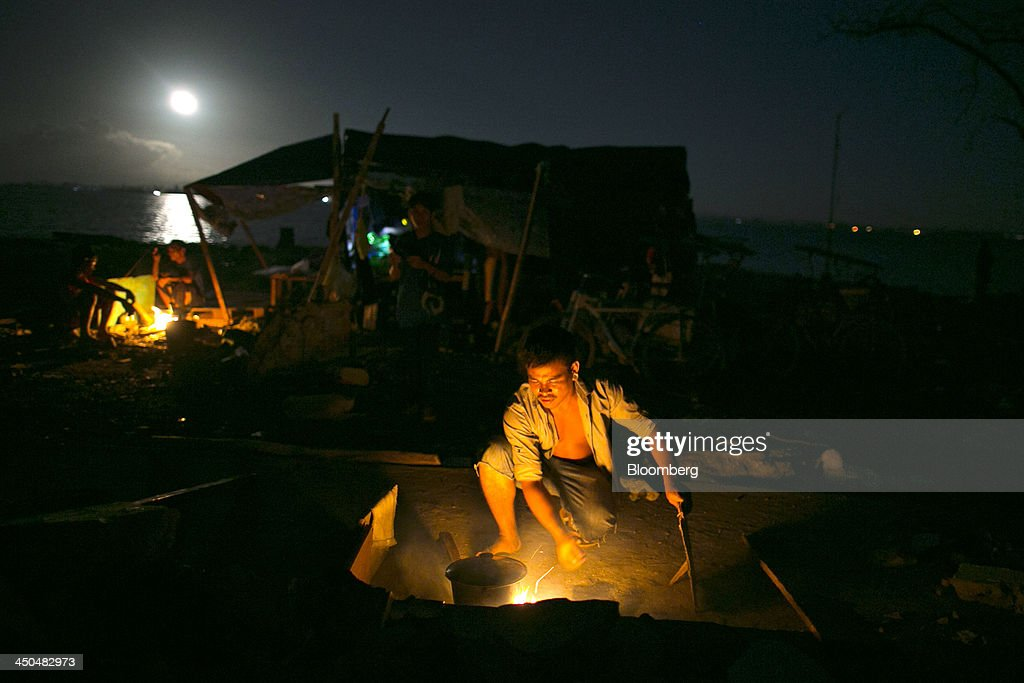 A man throws firewood into a flame as he cooks a meal under the full moon at a displaced person's camp in Tacloban, the Philippines, on Monday, Nov. 18, 2013. Super Typhoon Haiyan slammed into the central Philippines on Nov. 8, knocking down most buildings, killing thousands, displacing 4 million people and affecting more than 10 million. Photographer: Paula Bronstein/Bloomberg via Getty Images