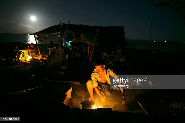A man throws firewood into a flame as he cooks a meal under the full moon at a displaced person's camp in Tacloban the Philippines on Monday Nov 18...