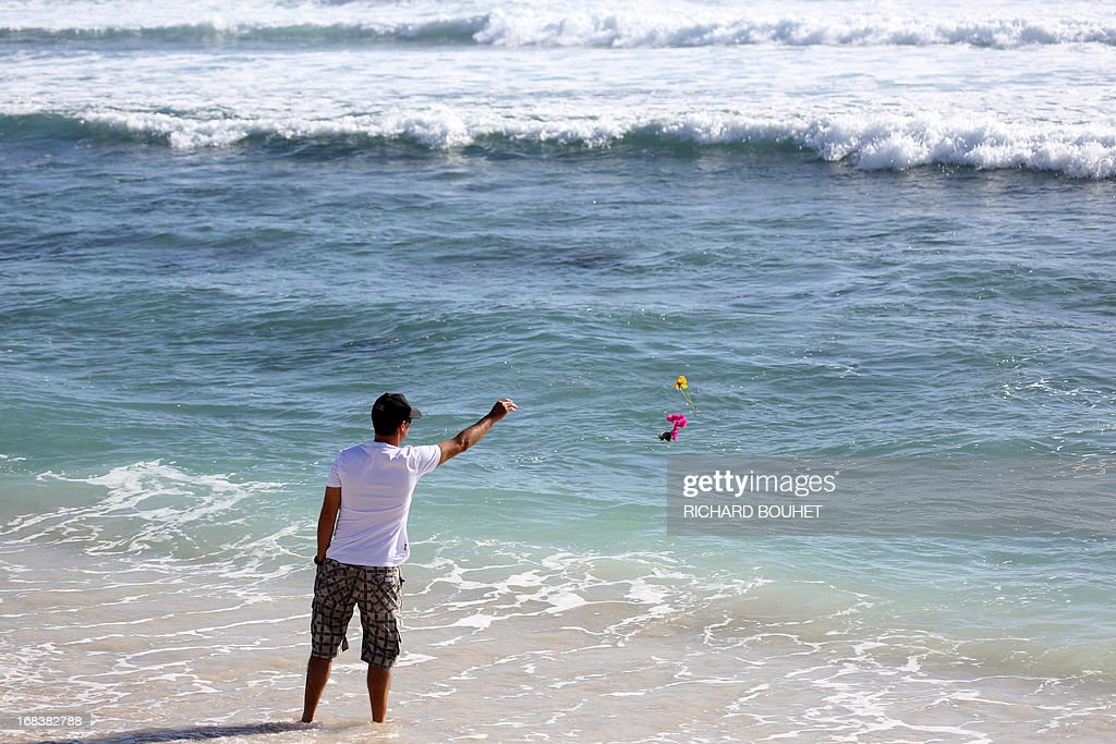A man throws flowers into the water off the beach of Brisants in Saint-Gilles-les Bains on May 9, 2013 to pay tribute to a surfer killed after he was attacked by a shark on May 8. The 36-year-old French honeymooner was in the sea off the popular beach of Brisants de Saint-Gilles when a shark charged at him twice, prompting a nearby swimmer to raise the alert when he saw blood on the water, the local prefecture said.