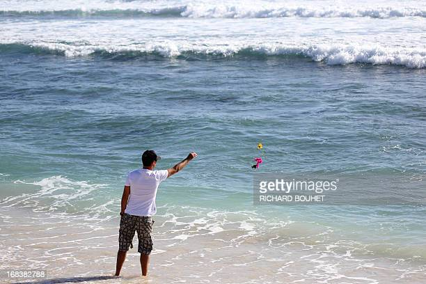 A man throws flowers into the water off the beach of Brisants in SaintGillesles Bains on May 9 2013 to pay tribute to a surfer killed after he was...