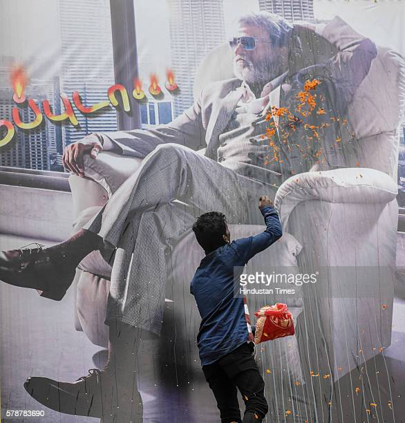 A man throws flowers on the banner of the Rajinikanth at Aurora Cinema Matunga on July 22 2016 in Mumbai India It was a sleepless night for the most...