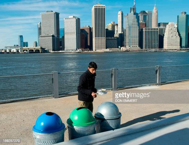 A man throws his trash away in color coded cans in Brooklyn Bridge Park January 10 2013 in New York Cans are color coded and marked for waste paper...