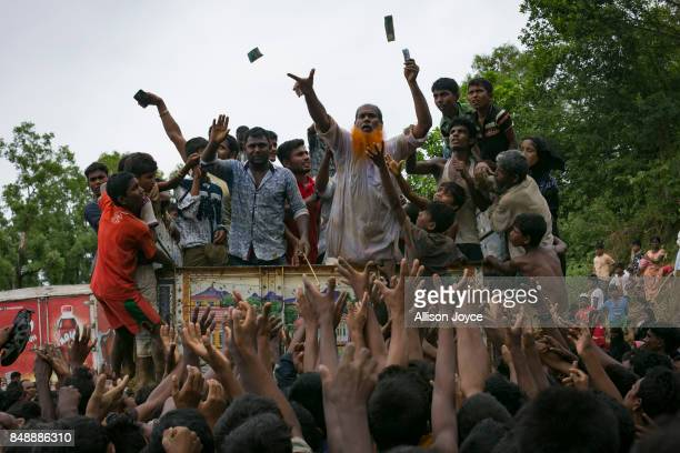 COX'S BAZAR BANGLADESH SEPTEMBER 18 A man throws money as refugees scramble for donations in the Balukhali camp on September 18 2017 in Cox's Bazar...