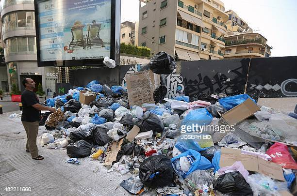 A man throws out his garbage on piles of rubbish on the street in Beirut on July 28 as the Lebanese capital and the surrounding region continue to...