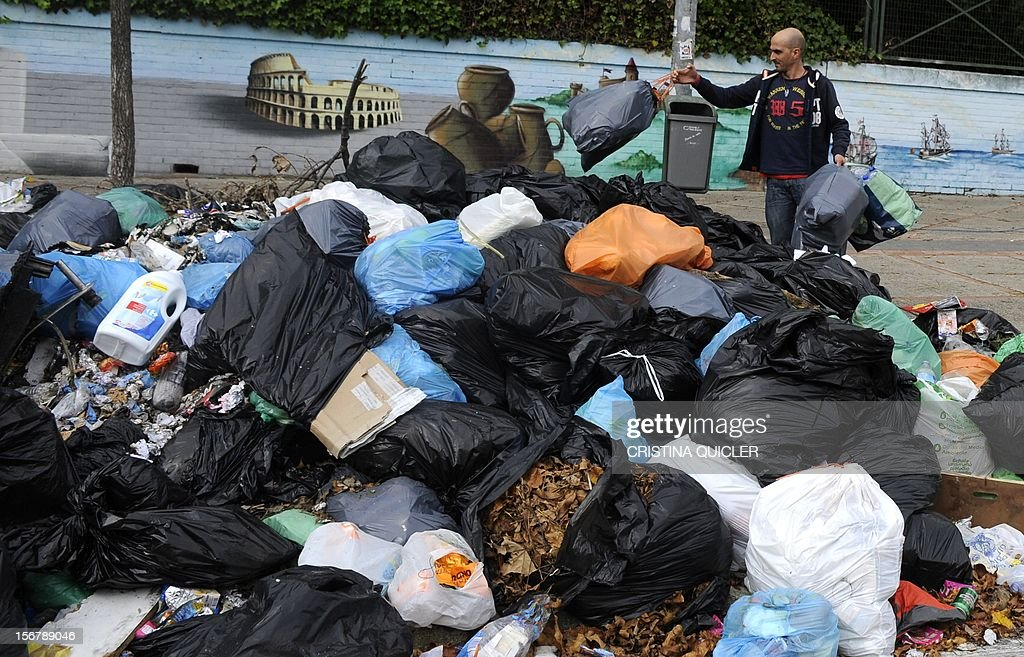 A man throws rubbish bags on a pile of uncollected rubbish in a street of Jerez de la Frontera on November 21, 2012. Rubbish collectors have been on strike in the municipality of Jerez de la Frontera since November 5, 2012 to protest against the austerity cuts imposed by the town hall.