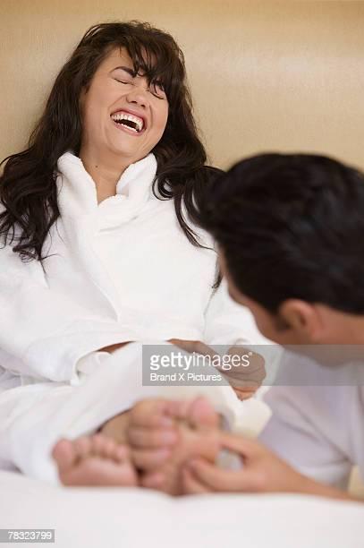 Man tickling feet of woman