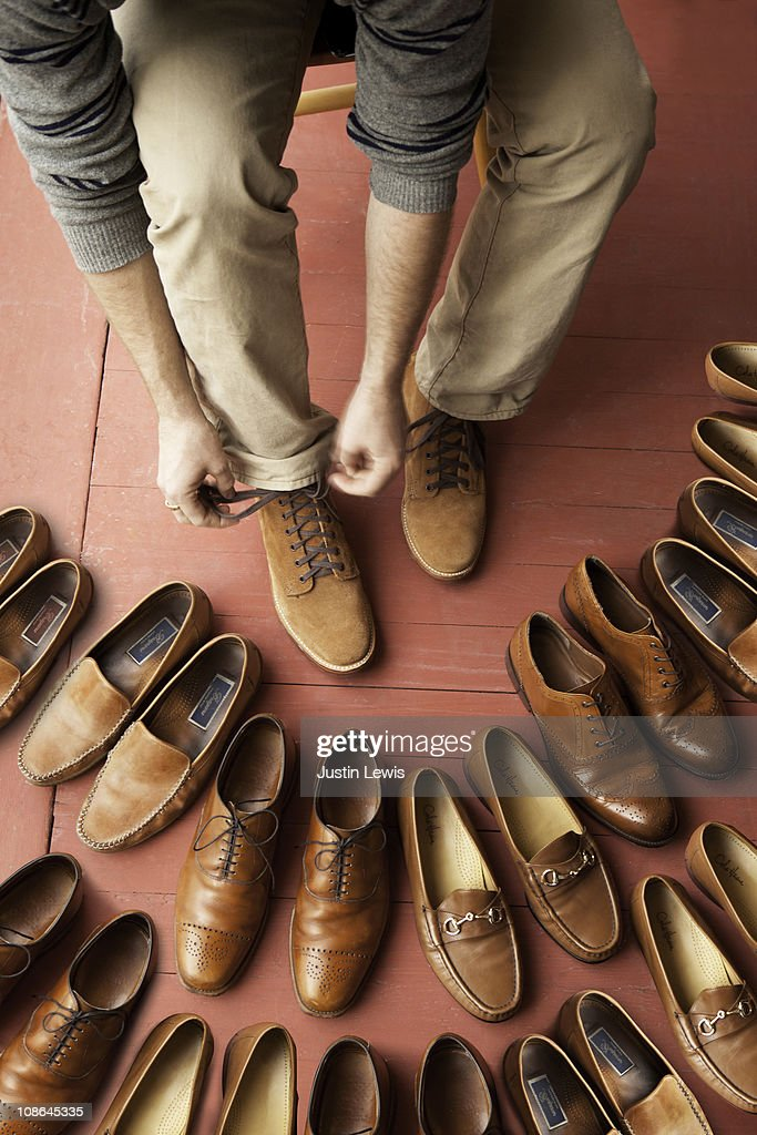 Man tieing his laces surrounded by lots of shoes : Stock Photo