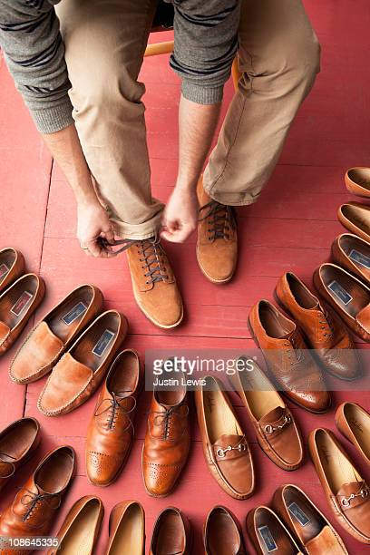 Man tieing his laces surrounded by lots of shoes