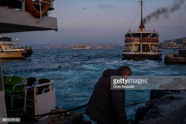 A man ties off a ferry at the Eminonu ferry terminals on March 10 2017 in Istanbul Turkey Turkey will hold its constitutional referendum on April 16...