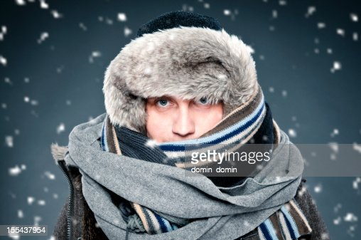 Man tightly bundled up in winter clothes, shawl, fur cap