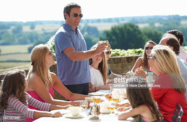 Man toasting at table outdoors