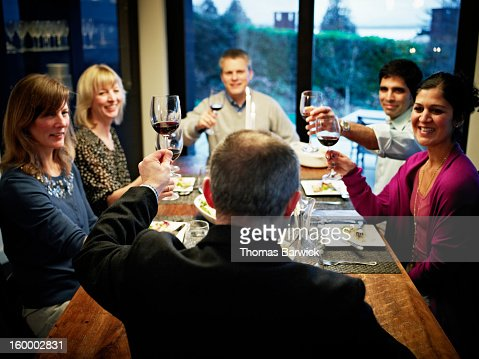 Man toasting wine glass with family and friends : Stock Photo