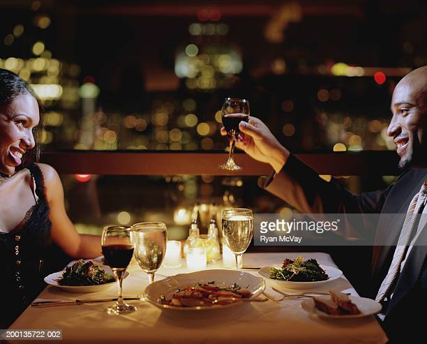 Man toasting woman at restaurant table, side view