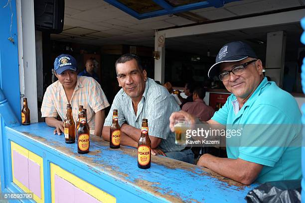 A man toasts with his beer glass while sat in a bar with his drinking partners on January 24 2016 in Filandia Colombia Filandia is a town and...