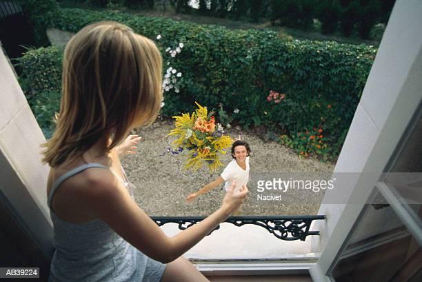 Man tossing bouquet of flowers to woman in open window