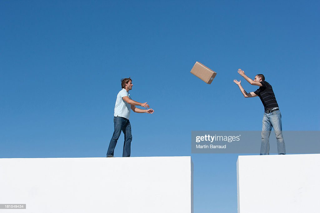 Man tossing cardboard box to man across gap outdoors with blue sky : Stock Photo