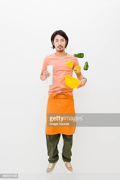 Man tossing peppers