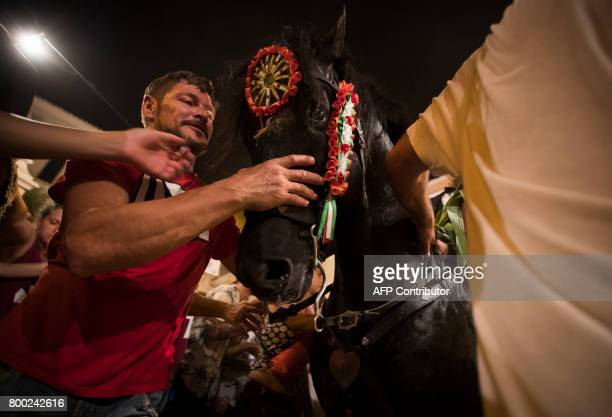 A man touches a horse during the traditional San Juan festival in the town of Ciutadella on the Balearic Island of Menorca in the night before Saint...