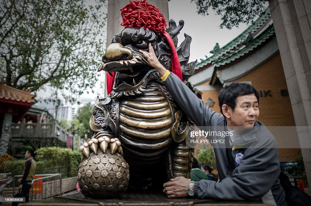 A man touches a statue for good fortune at the entrance of a Taoist temple in Hong Kong in Hong Kong on February 7, 2013. A stock market slide, escalated conflict between Japan and China and more Gangnam-styled success for South Korean singer Psy will shape the incoming Year of the Snake, say Asian soothsayers. February 10 marks the first day of the Lunar New Year across the region. AFP PHOTO / Philippe Lopez
