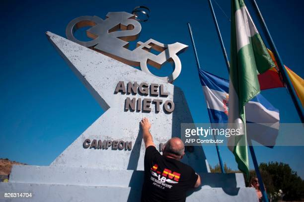 A man touches a tribute monument to Spanish former motorcyclist Angel Nieto during an homage at the Jerez racetrack in Jerez de la Frontera on August...