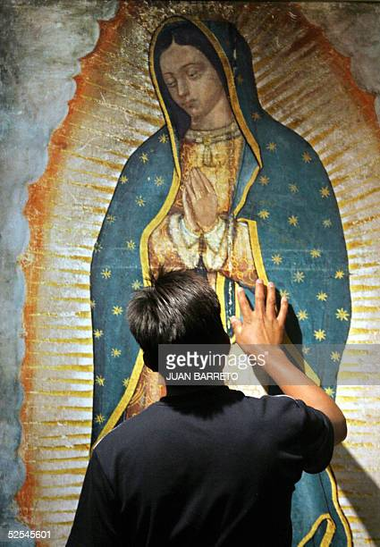 A man touches an image of Mexico's patron the Virgin of Guadalupe at the Basilica of the same name during a mass for Pope John Paul II 31 March 2005...