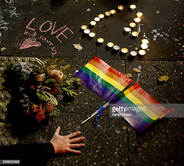 A man touches the ground next to rainbow flags during a candlelight vigil for the victims of the Pulse Nightclub shooting in Orlando Florida at...