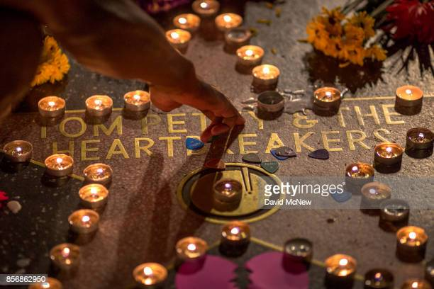 A man touches the Tom Petty and the Heartbreakers star on The Hollywood Walk of Fame after Petty suffered a massive heart attack last night that left...