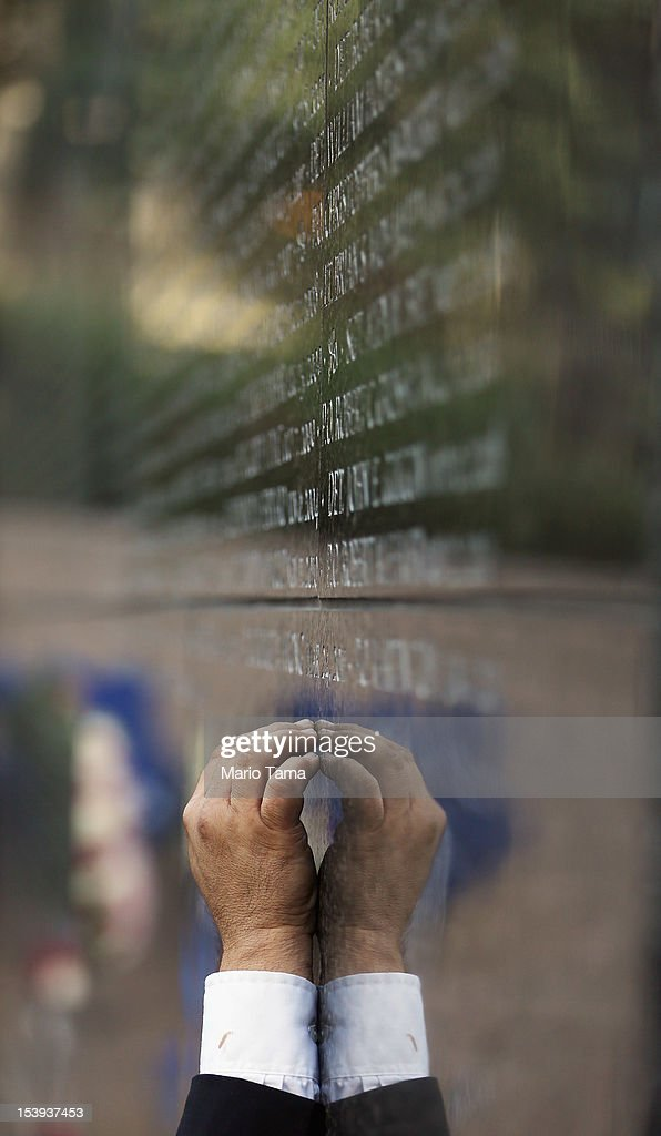 A man touches the wall during an unveiling ceremony at the New York City Police Memorial Wall on October 11, 2012 in New York City. The city unveiled the names of fiften officers who died last year.Thirteen succumbed to illnesses as a result of September 11 and two died from violence in Brooklyn.