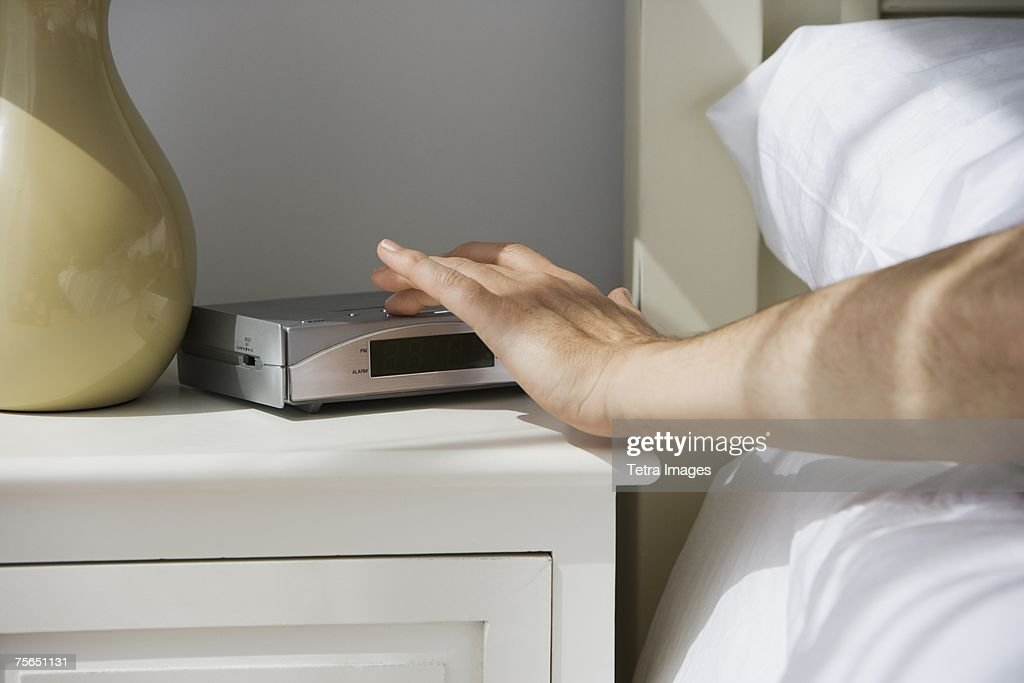 Man touching alarm clock from bed