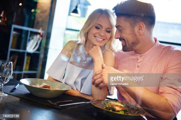 Man touching girlfriends arm at restaurant table
