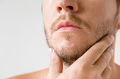 Man touching his short beard. Isolated on gray background. Men's issues. Face close up.