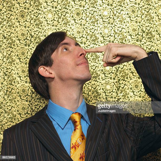 Man touching nose with finger