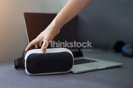 649fa7a607bc Man touching VR headset with earphone and laptop on sofa in living room  background