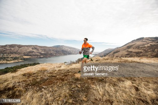 A man trail running along a beautiful gorge. : Stock Photo